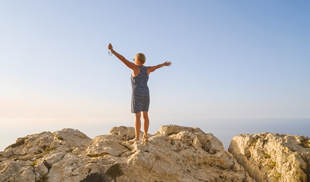 A women happily looks at the sky with her arms wide open.