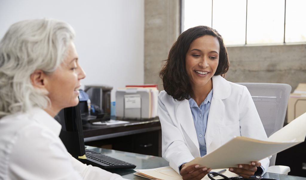 An old women consulting another doctor by discussing some reports.