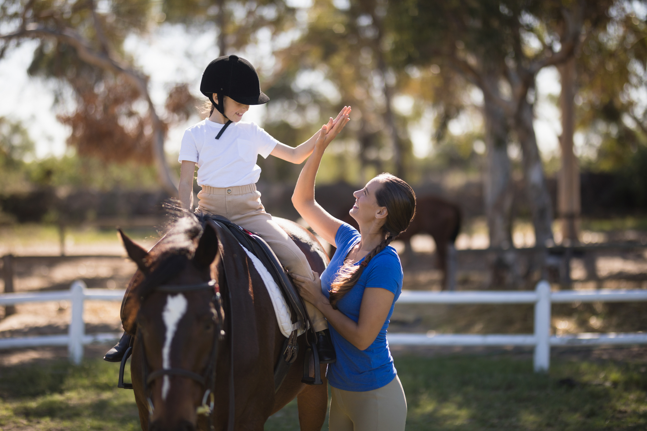 Child,fully prepared for a horse riding, gives a high five to a women