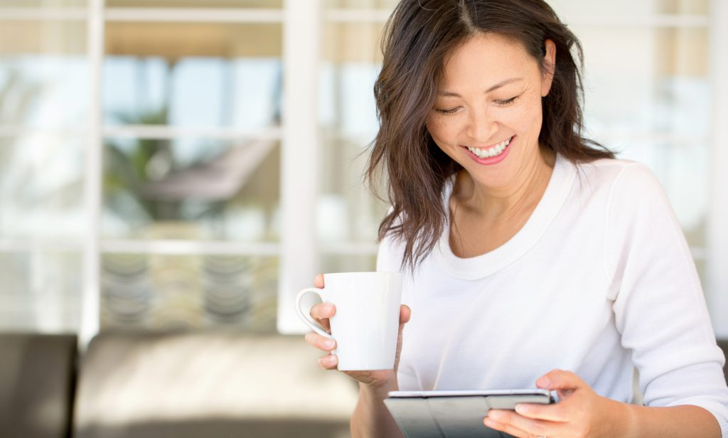 Women happily looking at her digital tablet while having a cup of coffee.