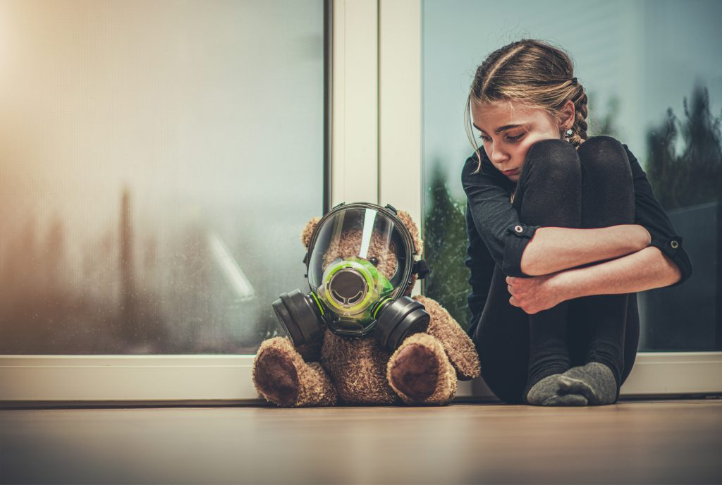 A small girl anxiously staring at her teddy who has put a mask on it.